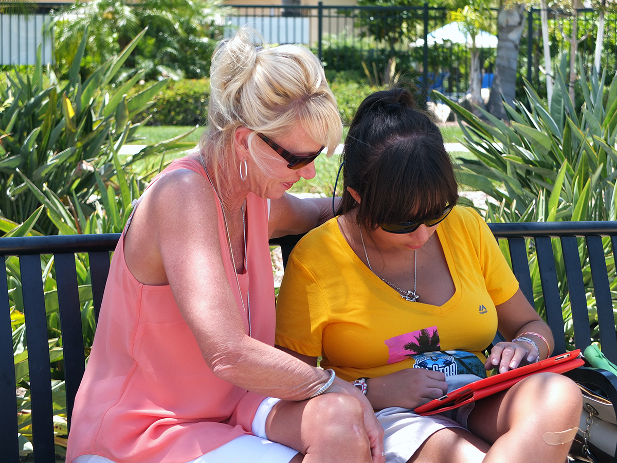 Mother helping daughter with disabilities navigate iPad.