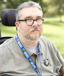 White man with a scruffy beard and glasses who also uses a wheelchair
