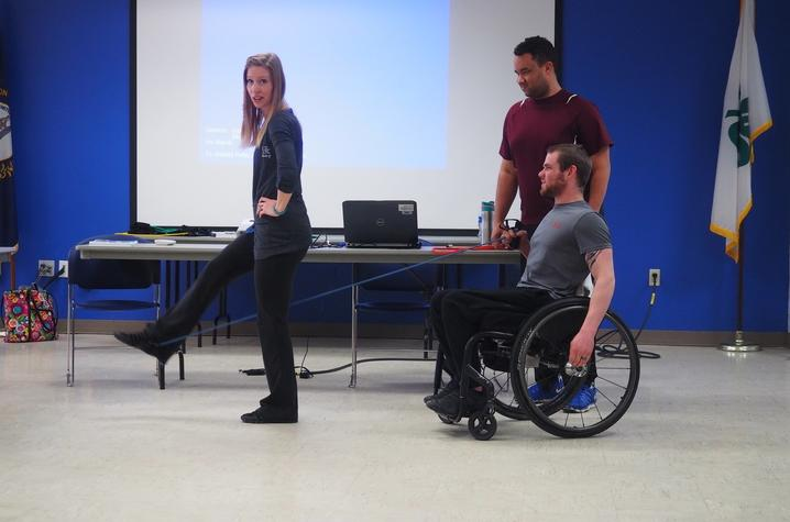 Two men, including one with prosthetics and one man using a wheelchair, exercising with a woman