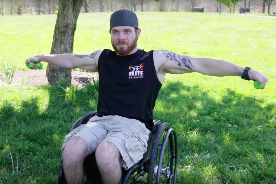 Athletic man in a wheelchair lifting weights.