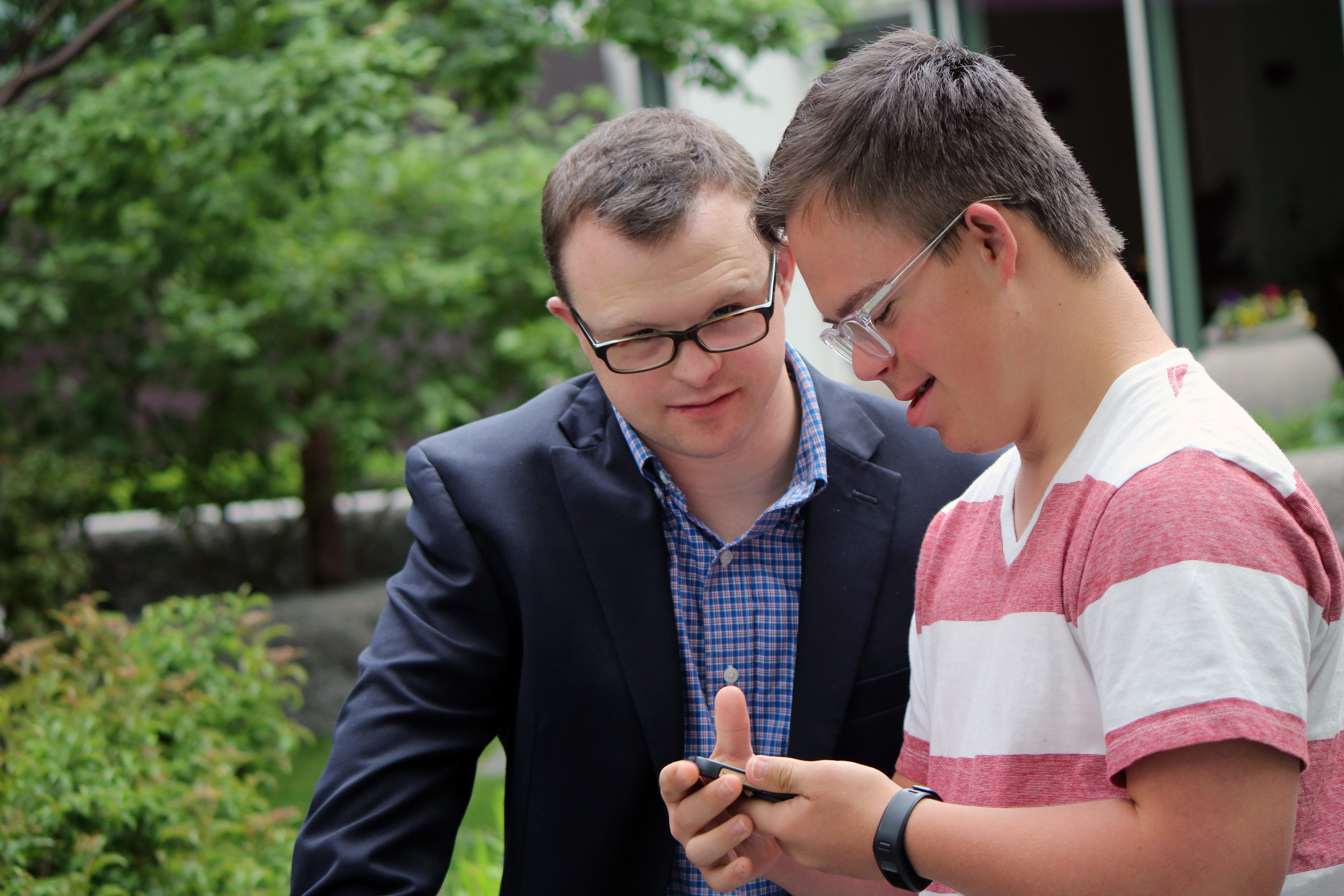 Two men with Down syndrome working on their phones.