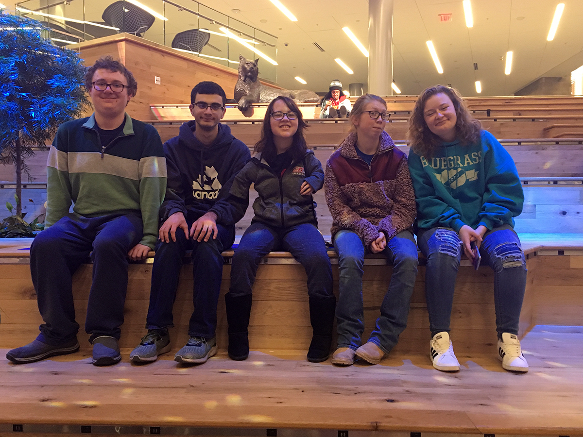 Five STEPS students sitting on a wall.