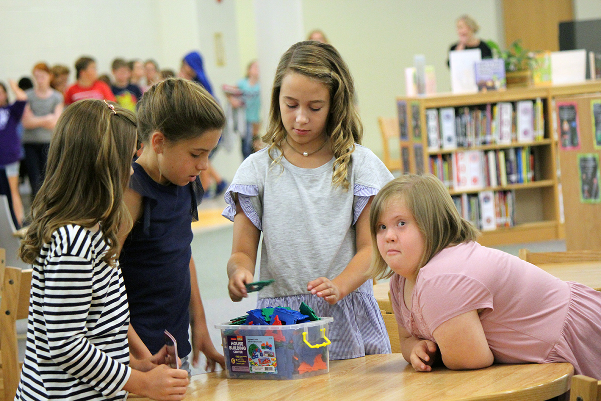 Four female students working together, including one with Down syndrome.