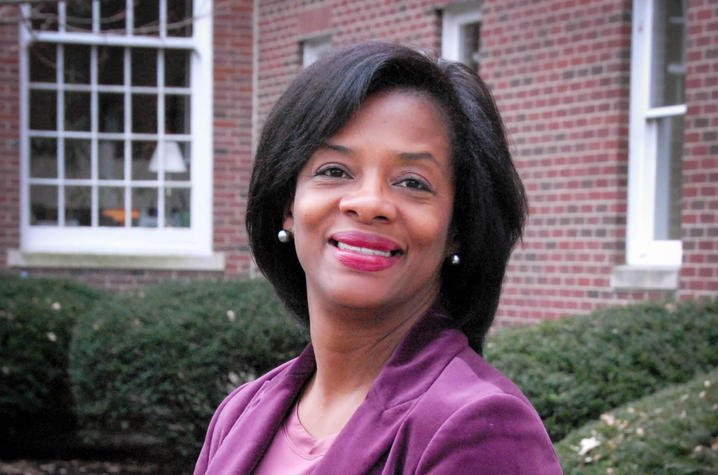 Middle-aged professional African American woman wearing a purple jacket