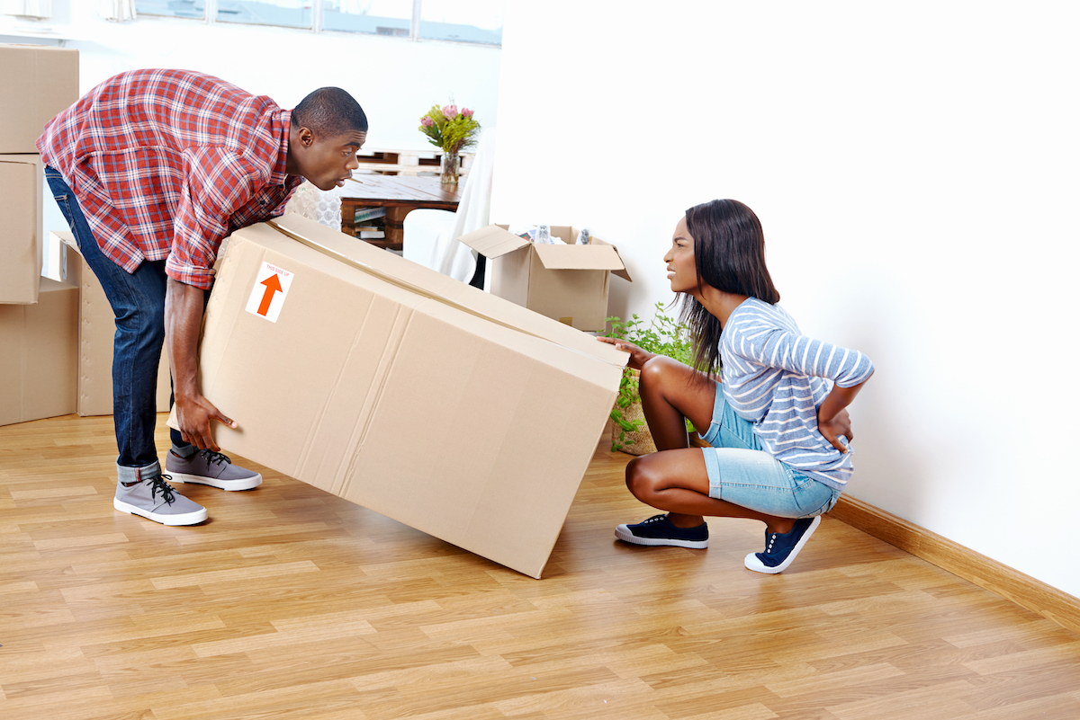 Man and woman lifting a box and woman grabbing back in pain.
