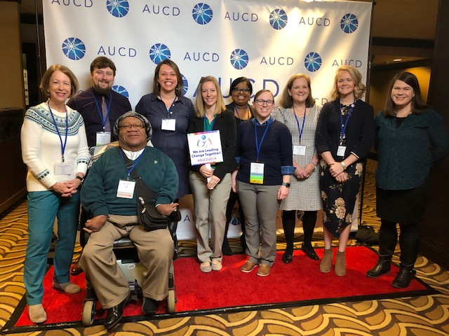 10 people in front of AUCD banner